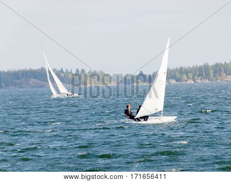KAPELLSKAER SWEDEN - JUL 28 2016: Two competing sailboats on the glittering blue sea a summar day. July 28 2016 in Kapellskaer Sweden