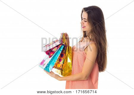 a young girl stands sideways and holding a bright beautiful bags isolated on white