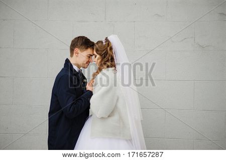 Young Wedding Couple At Cold Winter Day Against White Stone Wall Of Building.