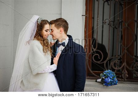 Young Wedding Couple At Cold Winter Day Against White Stone Wall Of Building With Wrought Iron Windo