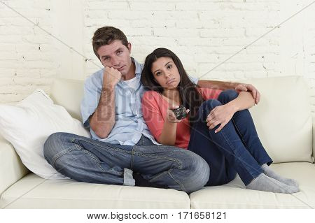 young couple watching television together at home sofa couch looking bored and frustrated switching channels with remote controller in boredom TV concept