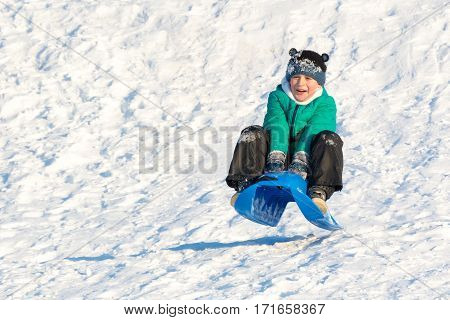 Boy Playing In The Snow. Sledding On A Snowy Hill. Winter Games. Baby Joy Of Snow. Throwing Snowball