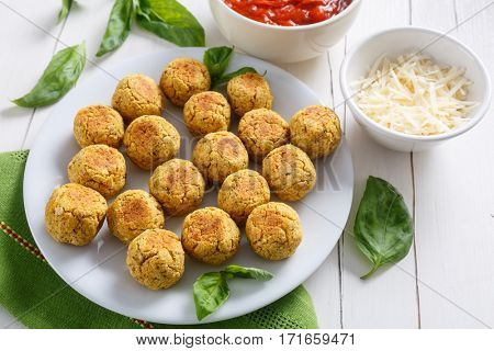 Plate of Spicy Chickpea Meatballs with tomato sauce, grated parmesan cheese and basil leaves
