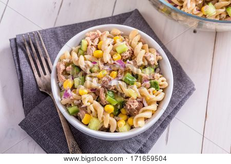 Two Bowls of Freshly-Cooked Pasta Salad with Tuna, Cucumber, Sweetcorn on a White Wooden Table
