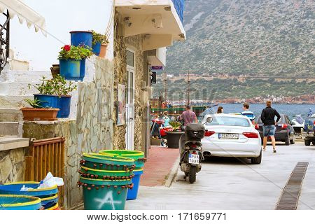 Bali Greece - April 30 2016: Two-wheeled moped and white car Audi A5 coupe parked on Mithos beach promenade in sea bay of resort village Bali. Classic Greek stone architecture of resort tourists walk streets of city. Rethymno Crete Greece