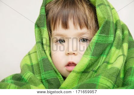 Cosy warm blanket furnishing child portrait in blanket warmingchildren care little girl wrapped in green warm blanketcomfortable winter concept