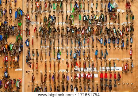 A lot of keys hanging on the wall. Keychain from the technical premises. Bunch of keys