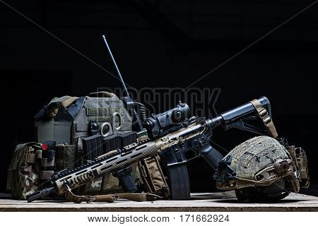 Body armor cover,assault rifle with a sight and helmet on black background