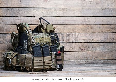 Military body armor,ammunition and ammo,radio and first aid tourniquet.On wooden table