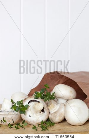 Button mushrooms and fresh thyme spilling from paper bag over white timber panelling.  Food background, with copy space.