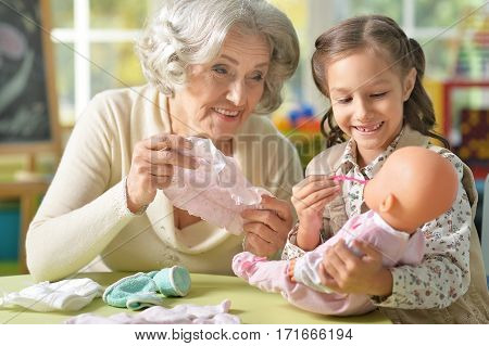 granny with granddaughter playing together with baby doll