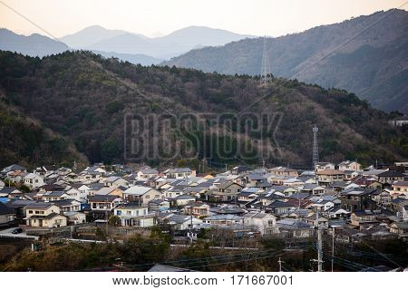 Wide angle view of the suburban houses of Nobeoka Kyushu Japan surrounded by mountains covered in trees. Early spring. Travel and tourism concept.