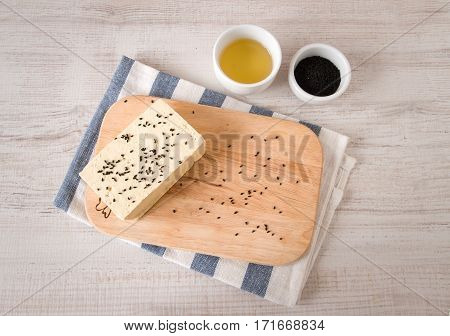 Fresh raw tofu on shabby cutting board with black cumin seeds and olive oil