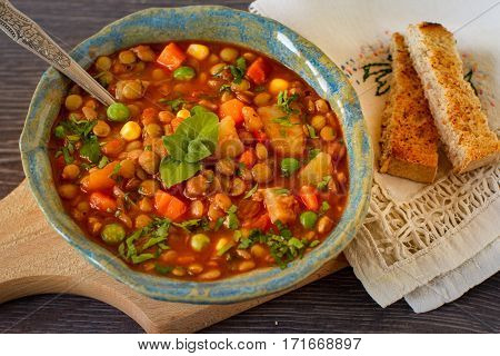 Vegetarian lentil stew with bolognese sauce in a bowl with parsley on rustic wooden table. Top view.