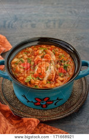 Italian lentil stew with bolognese sauce and sausage in a bowl with parsley on rustic wooden table