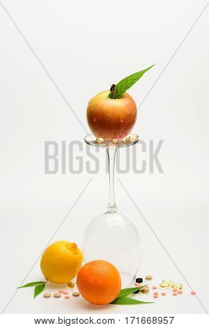 set of orange apple with drops lemon and wineglass with pills and capsule isolated on white background side view