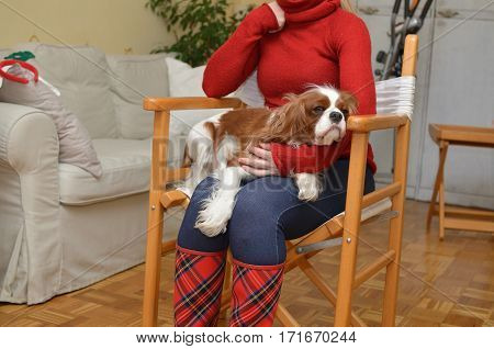 Woman in red boots with red tartan pattern holding her charmin dog Cavalier King Charles Spaniel