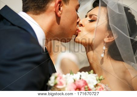 The bride and groom kissing on the street