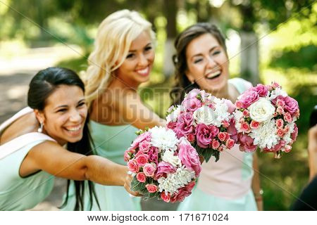 The smilling bridesmaids with bouquets of white and pink flowers