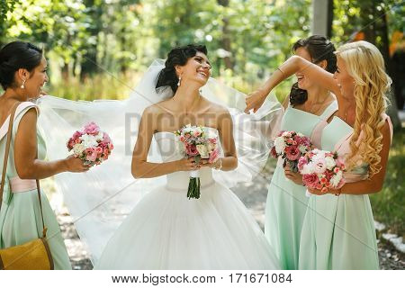 Elegant bridesmaids admiring of the bride on the street