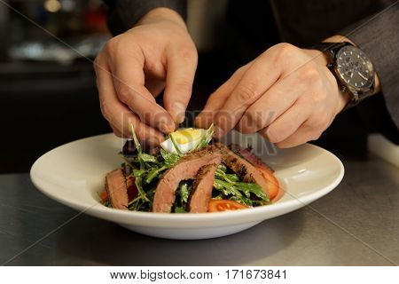 Professional chef is making appetizer with meat in commercial kitchen