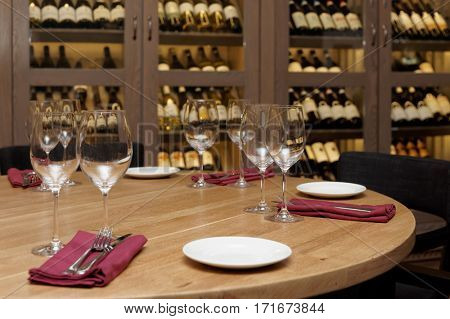 Restaurant table with wine cellar in blurred background