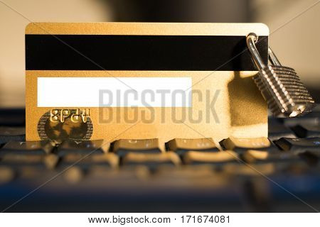 Credit card with small hanging padlock on keyboard