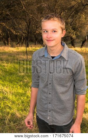 Blond Young Boy Stading in Green Grassy Field