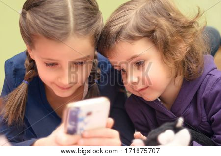 Two little girls with smartphone lying on bed at home. Small girls playing mobile games.