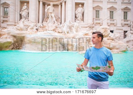 Happy young man with city map in Vatican city and St. Peter's Basilica church, Rome, Italy. Travel tourist guy outdoors on holidays in Europe.