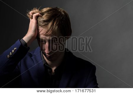 young man in suit businessman holds his hand behind her head on a neutral fone.oschuschenie sadness, pain, deperess