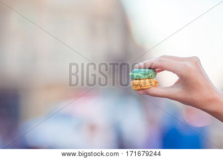 Girl holding colorful French macarons in hands