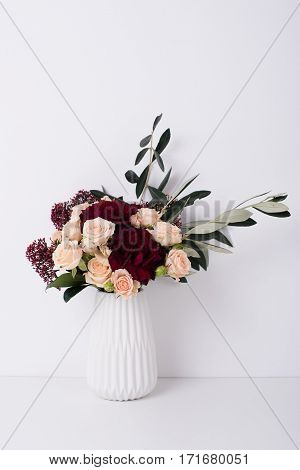 Beautiful bouquet of roses and carnations in a vase in white interior with copyspace. Elegant home decor.