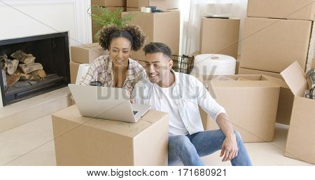 Happy couple using laptop in their new apartment