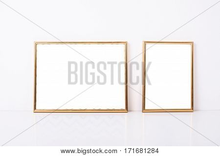 Two golden frames mock-up on white wall background, home decor objects