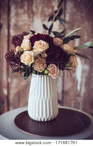 Beautiful bouquet of roses and carnations in a vase, vintage style. Elegant home decor.