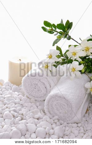 Towel and candle and gardenia on white pebbles