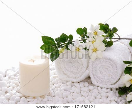 gardenia with candle towel on white pebbles