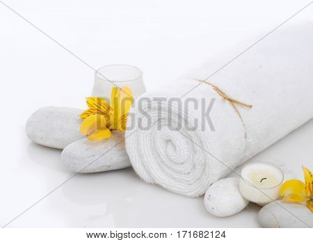 Spa setting with candle, stones,towel, orchid
