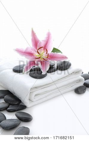Pile of black stones and lily on towel –white background