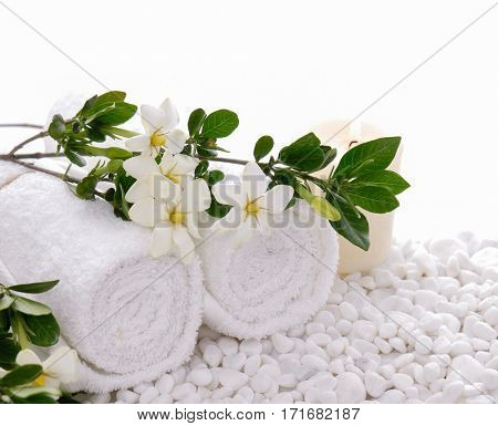Beautiful white Gardenia laying ,towel, with candle onwhite stones background