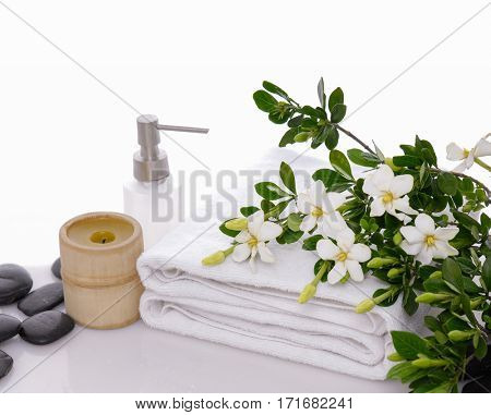 gardenia on towel with black stones,candle, oil on white background