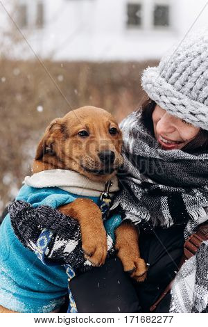 Stylish Hipster Girl Hugging And Caressing Cute Puppy In Snowy Cold Winter Park. Moments Of True Hap