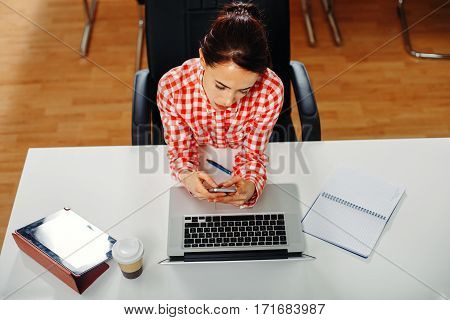 Women in the office typing a message on the phone