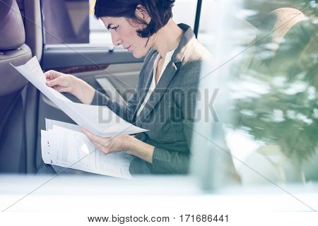 Businesswoman reading documents on backseat of the car