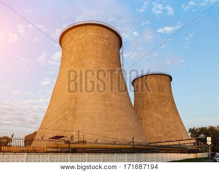 Cooling towers of the power plant on the sky background
