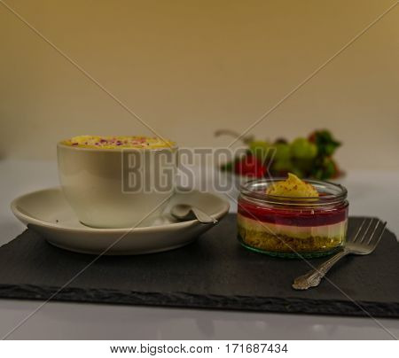 black coffee in a white cup on a saucer with whipped cream and spoon and forks and creamy strawberry dessert on a black stone plate in the bacground fresh fruits