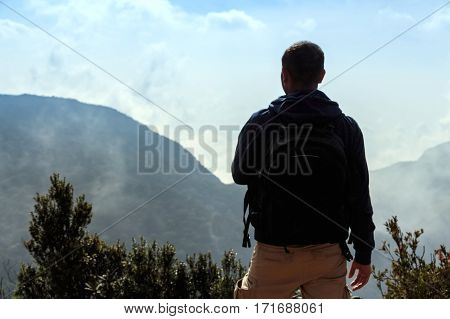 Hiker is standing on the edge of abyss above vast forest territory of foggy mountains in Sri Lanka