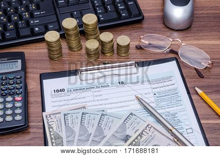 1040EZ income tax form with money pen on table