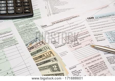 1040 tax form with pen dollar and calculator